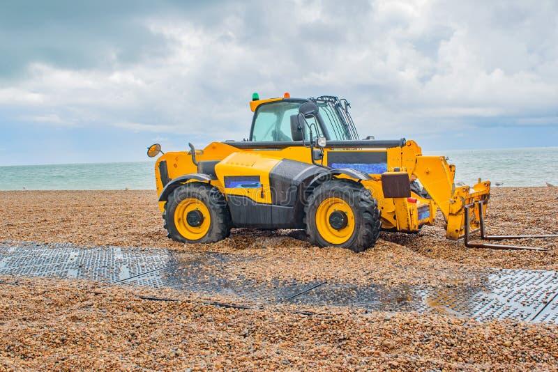 A big yellow tractor on Brighton beach stock photos