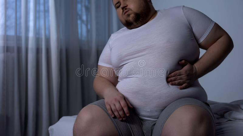 Big young man suffering from stomach pain, acid reflux, fat liver disease, diet royalty free stock photography
