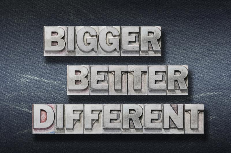 Bigger, better, different den. Bigger, better, different words made from metallic letterpress on dark jeans background royalty free stock images