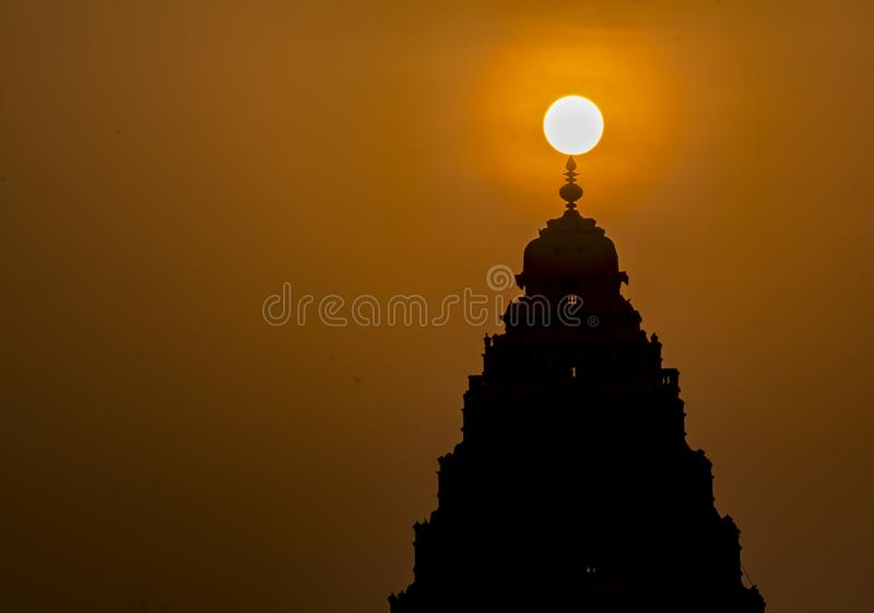 Sunrise: Natural Light decoration over a Hindu temple. Biggest light of the earth, forming the apex of a hindu temple, giving it a clear silhouette view during royalty free stock photos