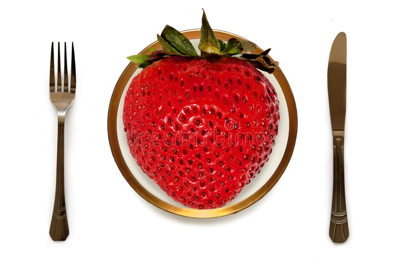 Biggest strawberry on your plate; folk, knife stock image