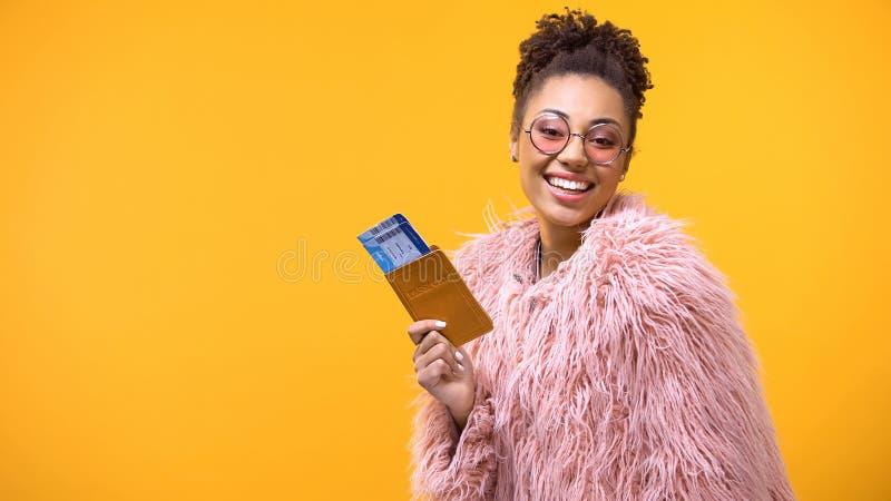 Biglietti africani sorridenti del passaporto e di viaggio di rappresentazione della donna su fondo giallo immagini stock