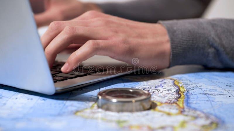 Biglietti d'acquisto dell'uomo attivo online sul computer portatile, sulla vacanza di progettazione o sul viaggio di affari fotografie stock libere da diritti