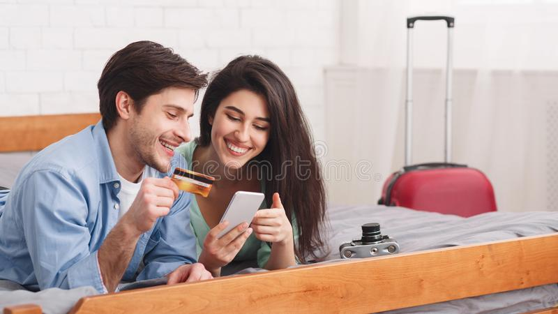 Biglietti di prenotazione di amore delle coppie facendo uso del telefono e della carta di credito fotografia stock