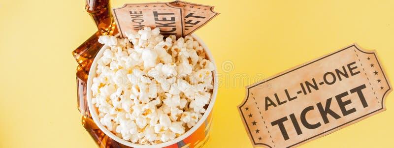 Biglietti, strisce di pellicola e popcorn di film su fondo blu Copi lo spazio per testo immagini stock libere da diritti