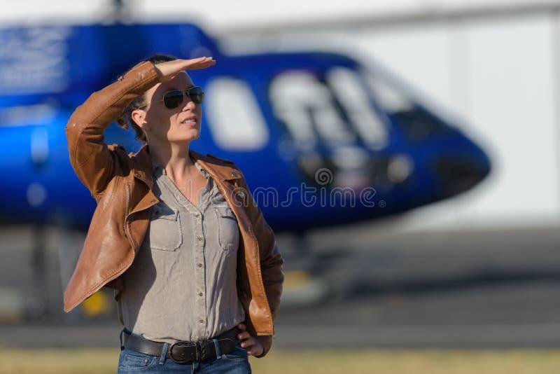 Biglietto d'ordinazione di giro dell'elicottero della giovane donna dalla compressa sull'aeroporto immagine stock