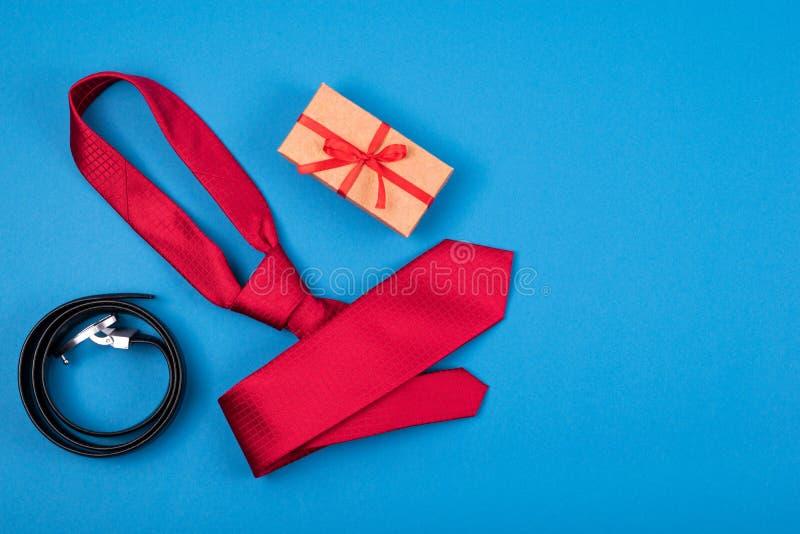 Biglietto di auguri con composizione di cravatta del collo rosso e scatola regalo con arco e cintura su fondo ciano blu immagini stock