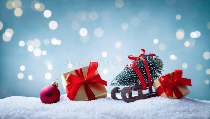 Biglietto di auguri di Natale Scatole di regalo e slitta con abete decorativo su fondo di neve Striscione festivo fotografie stock