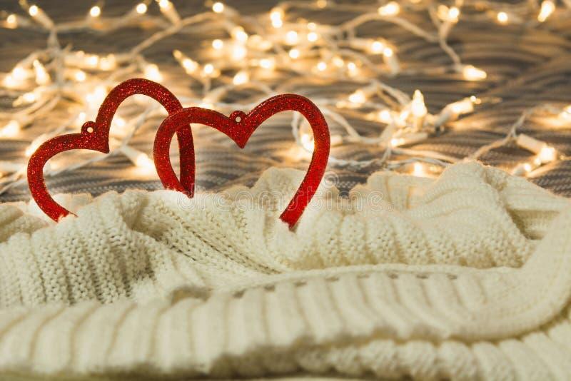 Biglietto di S. Valentino e concetto di amore con due cuori in plaid caldo con le luci su fondo fotografia stock