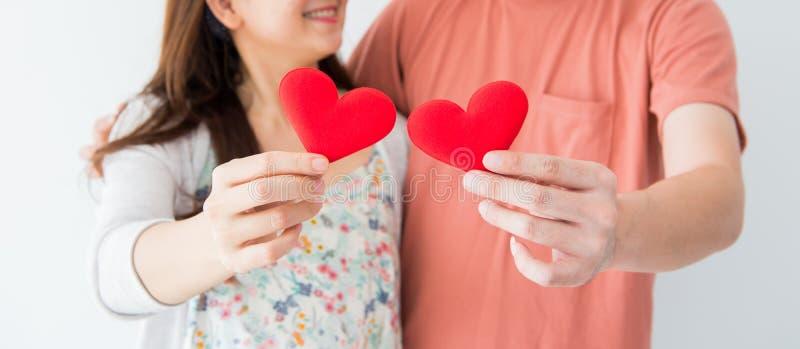 Biglietto di S. Valentino e giorno più dolce, cuore rosso sulle mani delle coppie fotografia stock