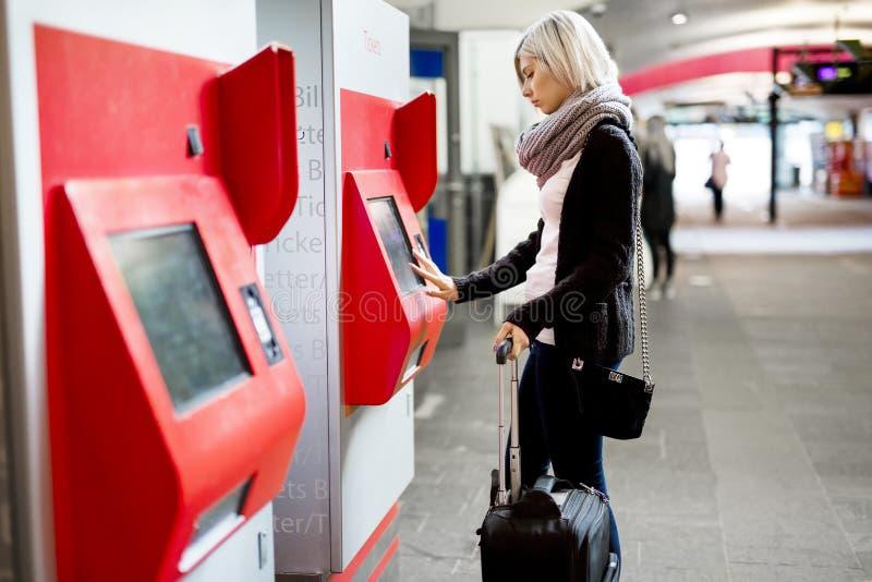 Biglietto di treno d'acquisto della donna facendo uso del distributore automatico alla stazione fotografie stock