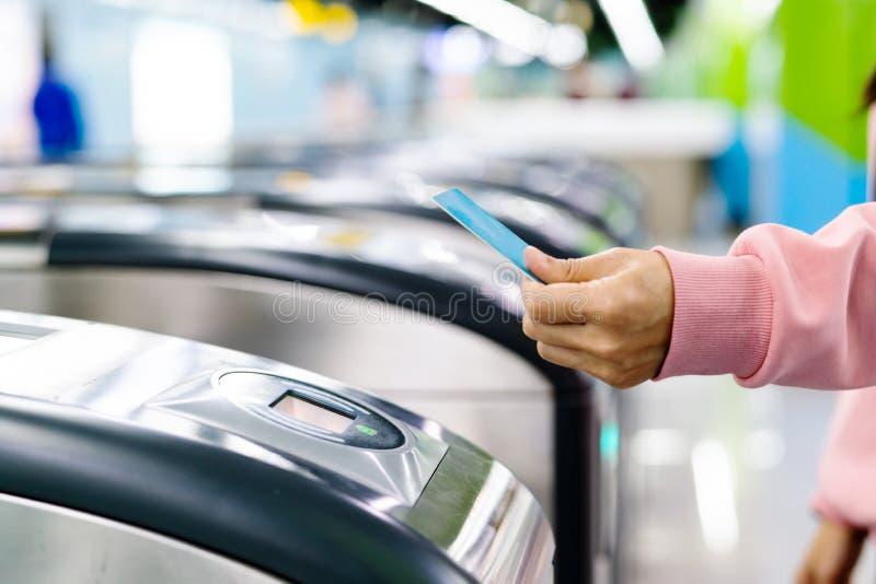 Biglietto di treno di esame della mano della donna al portone dell'entrata del sottopassaggio Concetto del trasporto immagine stock libera da diritti