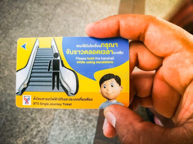 Biglietto di treno ferroviario della metropolitana di BTS con la tenuta della mano dell'uomo immagini stock