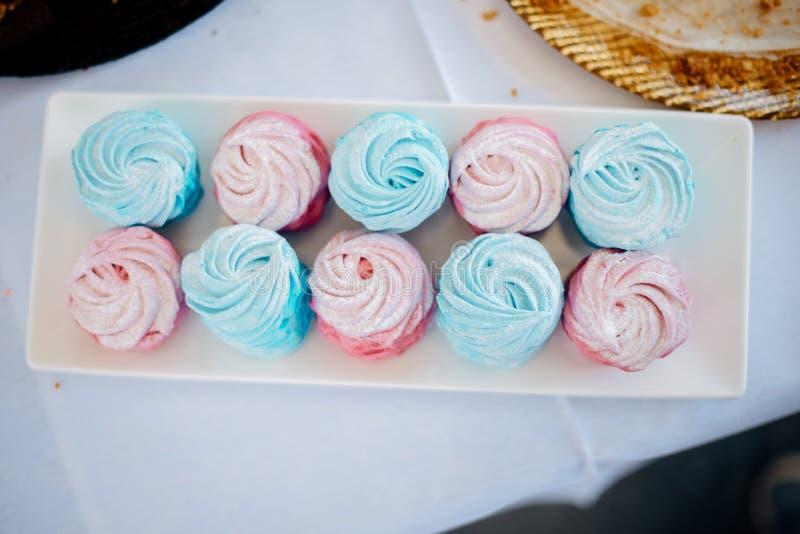 Bigné blu e rosa su un piatto bianco fotografie stock libere da diritti