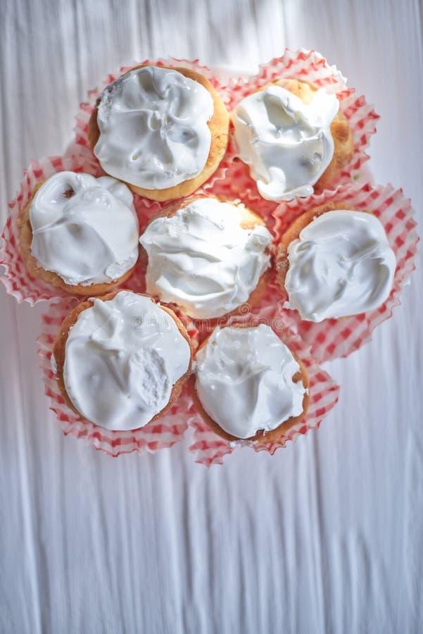 Bigné con crema bianca su un fondo di legno fotografia stock
