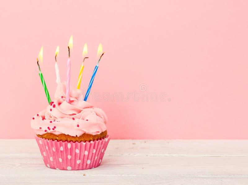 Bigné con crema e con cinque candele fotografia stock libera da diritti