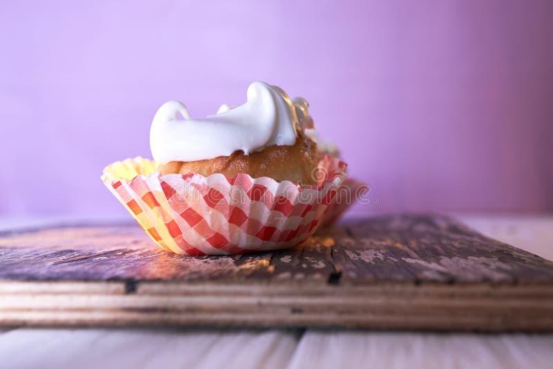 Bigné con crema su un fondo pastello su una tavola di legno fotografia stock libera da diritti