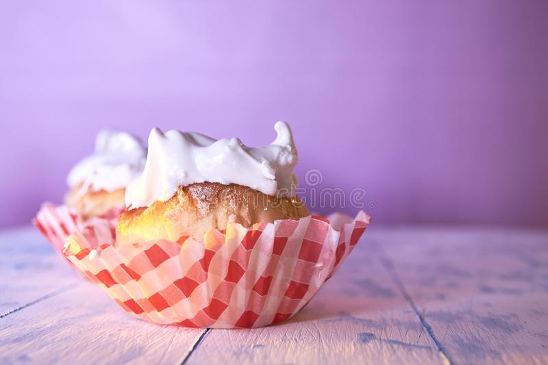 Bigné con crema su un fondo pastello su una tavola di legno fotografia stock