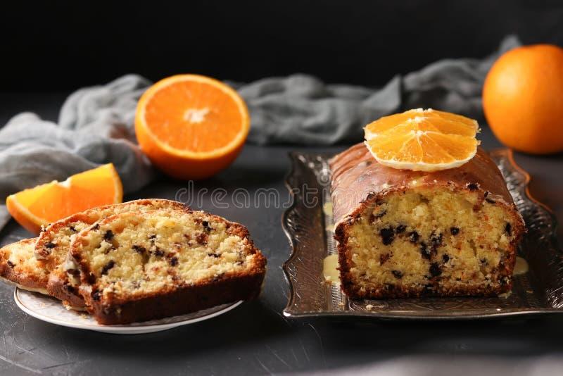 Bigné con le arance ed il cioccolato situati su un vassoio contro un fondo scuro fotografia stock libera da diritti