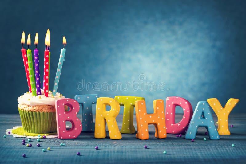 Bigné con le candele di compleanno fotografie stock