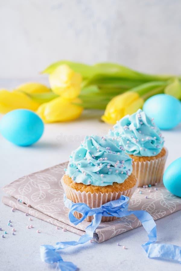 Bigné decorati con crema, le uova blu ed i tulipani per Pasqua fotografia stock libera da diritti