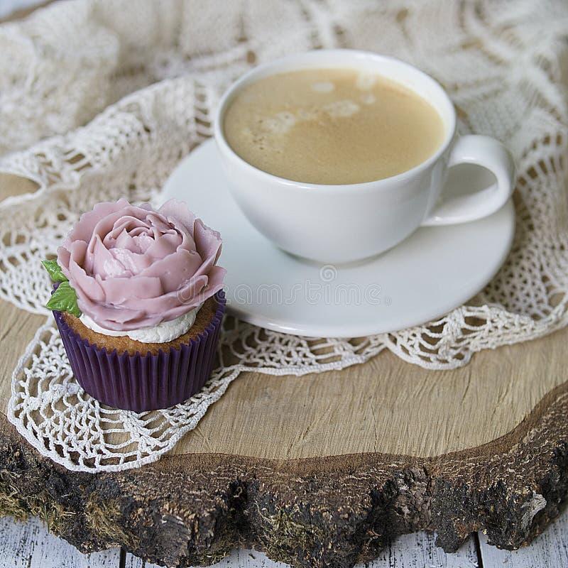 Bigné decorati con i fiori crema: è aumentato su un fondo di legno con un tovagliolo di pizzo con la tazza di caffè Scheda festiv immagini stock