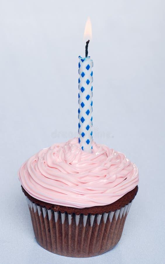 Bigné del cioccolato con glassare e la candela di colore rosa fotografia stock