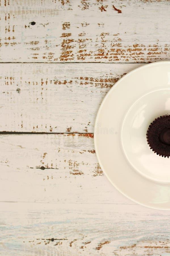 Bign? del cioccolato di Brown con materiale da otturazione crema su un piatto bianco sulla tavola con i bordi miseri immagine stock