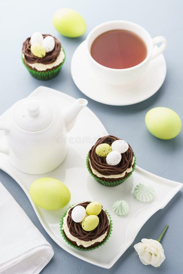 Bigné del cioccolato di Pasqua con le uova di caramella e del nido per il dessert immagine stock
