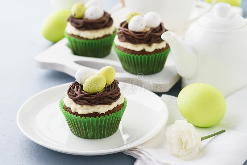 Bigné del cioccolato di Pasqua decorati con le uova di caramella e del nido immagini stock libere da diritti
