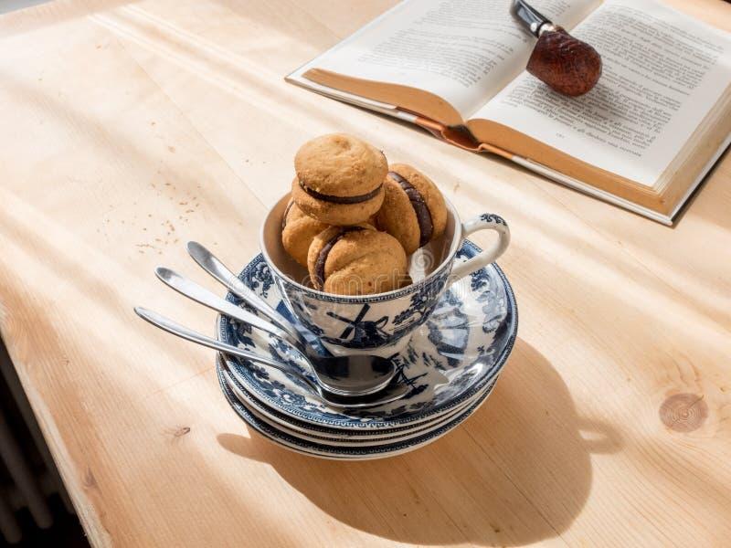 Bigné del cioccolato in tazza da the, libro su fondo fotografia stock
