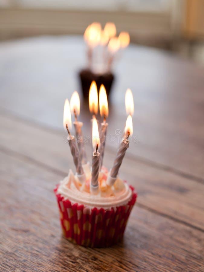 Bigné di compleanno con i lotti delle candele accese fotografia stock