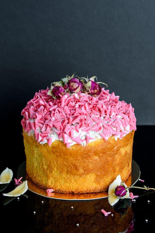 Bigné dolce ed appetitoso con la spruzzatura rosa sul nero fotografie stock libere da diritti