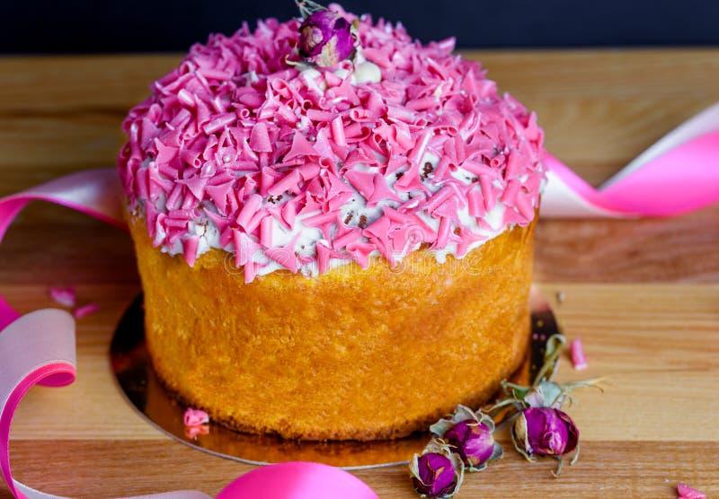 Bigné dolce ed appetitoso con la spruzzatura rosa sulla tavola fotografie stock