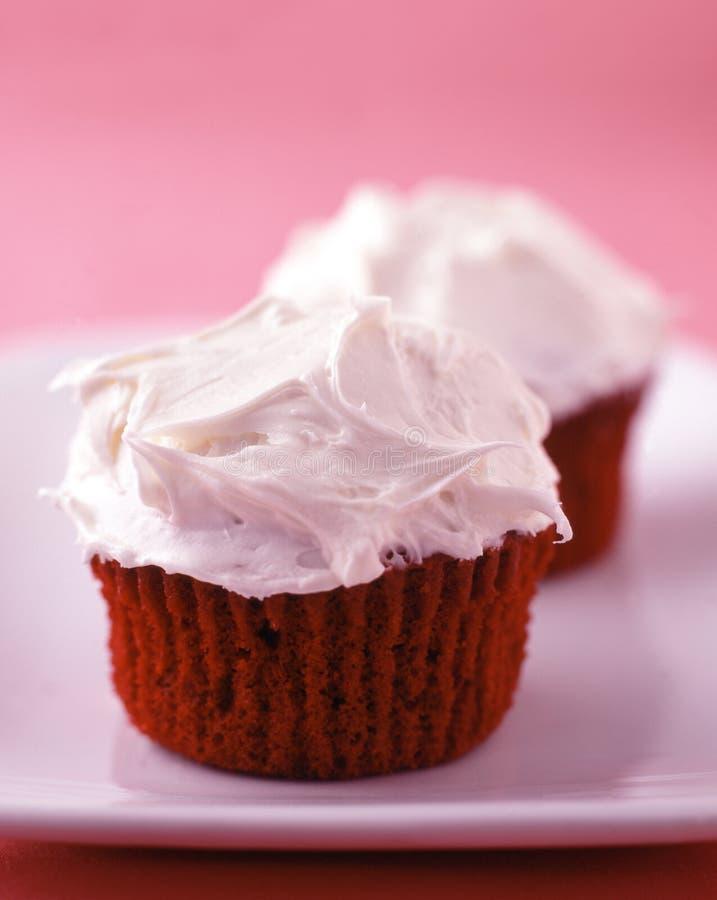 Bigné rossi del velluto con glassare della vaniglia fotografia stock libera da diritti