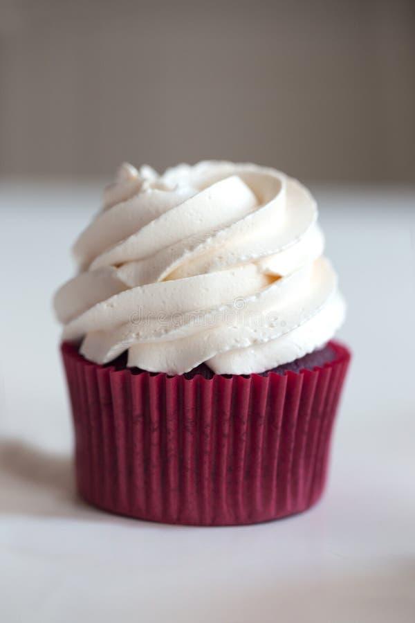 Bigné rossi del velluto I bigné hanno completato con il turbinio di glassare dolce della vaniglia fotografia stock libera da diritti