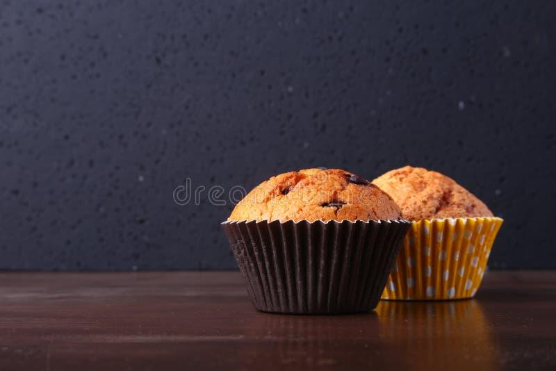 Bigné saporiti del cioccolato, muffin su una tavola di legno bianca fotografie stock libere da diritti