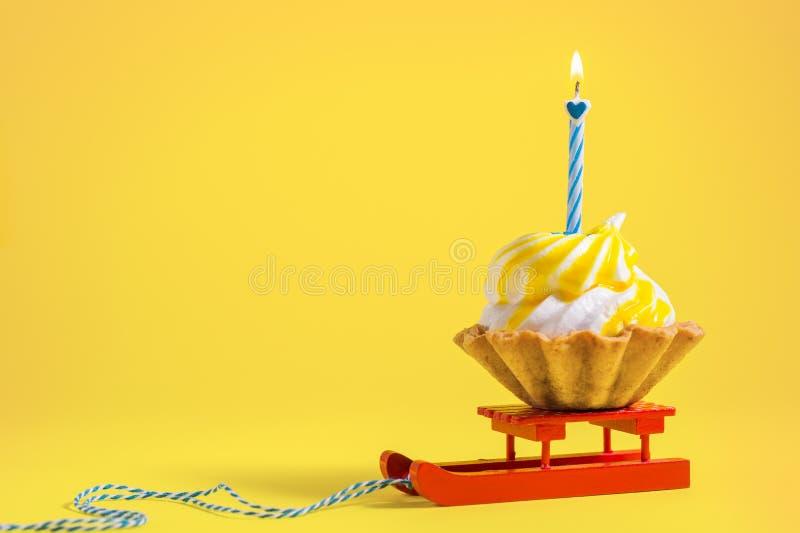 Bigné saporito di compleanno con la candela su fondo giallo con lo spazio della copia Muffin delizioso sul fondo di colore immagine stock