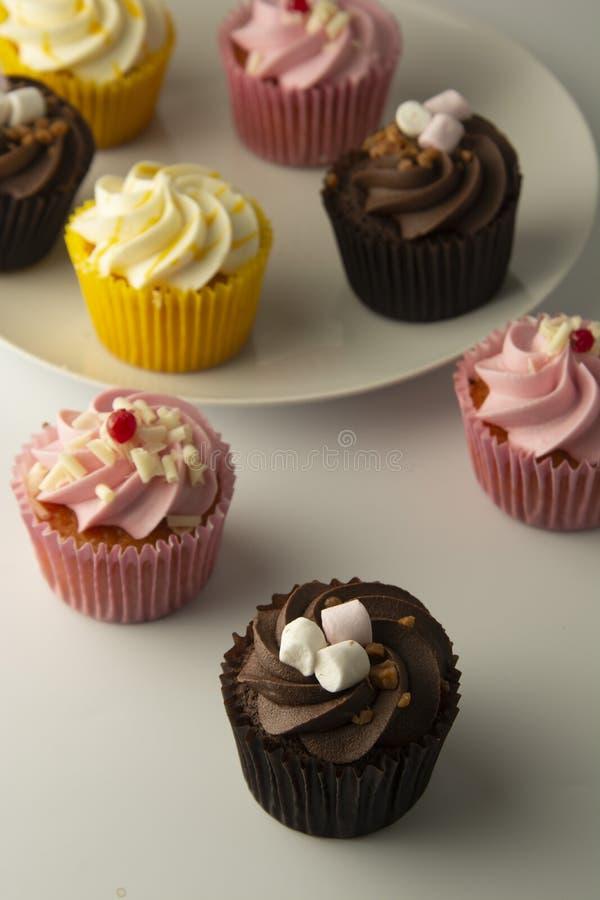 Bigné variopinti su una priorità bassa bianca Bigné gialli e del cioccolato di rosa, Spuntini saporiti Partito dolce della prima  fotografie stock libere da diritti