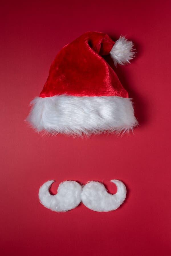 Bigode do moderno e chapéu brancos de Santa Claus no fundo vermelho foto de stock royalty free
