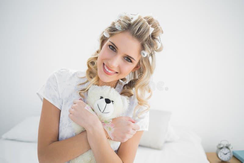 Bigodini d'uso biondi graziosi sorridenti che tengono orsacchiotto fotografia stock