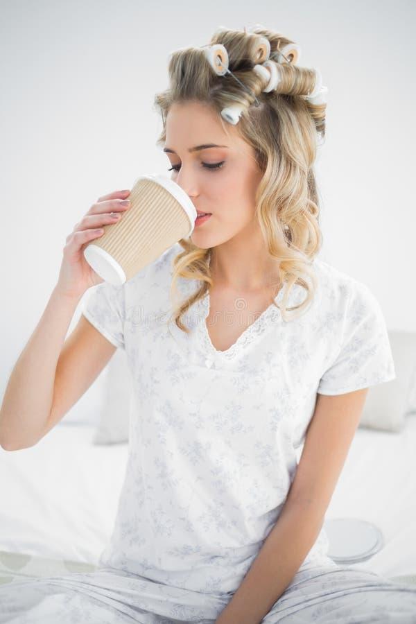 Bigodini d'uso della bionda graziosa pacifica che bevono caffè fotografie stock