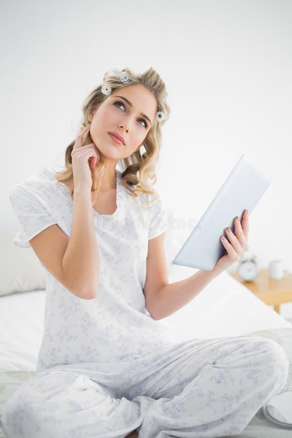 Bigodini d'uso della bionda sveglia premurosa facendo uso della compressa fotografie stock