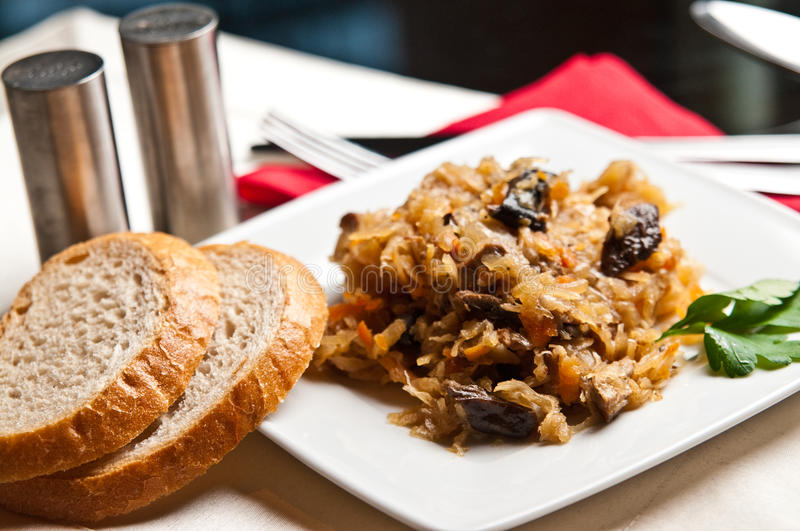 Bigos (Polish cuisine of cabbage food). An elegant plate of traditional Polish food bigos (cabbage served with meat, mushrooms and spices royalty free stock photos