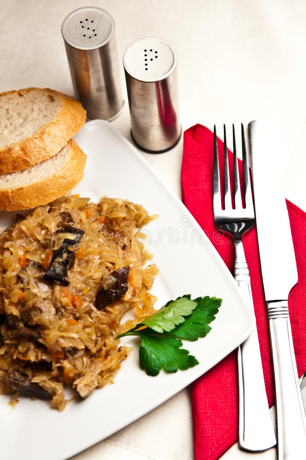 Bigos (Polish cuisine of cabbage food). An elegant plate of traditional Polish food bigos (cabbage served with meat, mushrooms and spices royalty free stock images