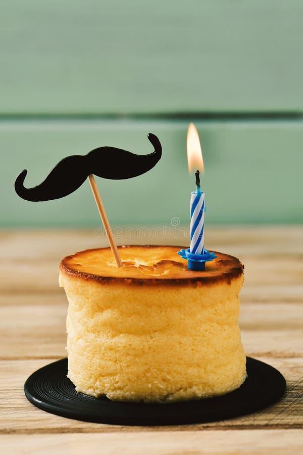 Bigote y vela encendida en un pastel de queso imagenes de archivo