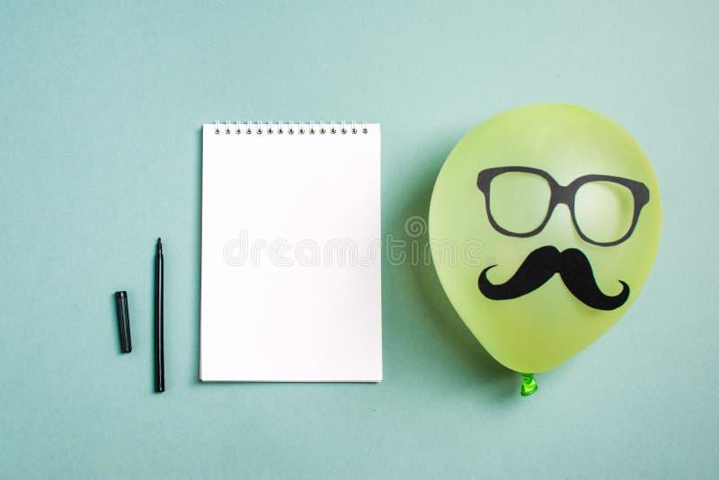 Bigote y vidrios de papel negros en el globo y una libreta con un rotulador imagenes de archivo