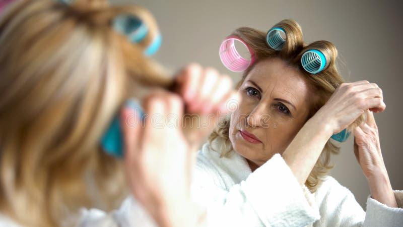Bigoudis de cheveux femelles retirés de fixation et préparation à la date romantique, aspect photos libres de droits