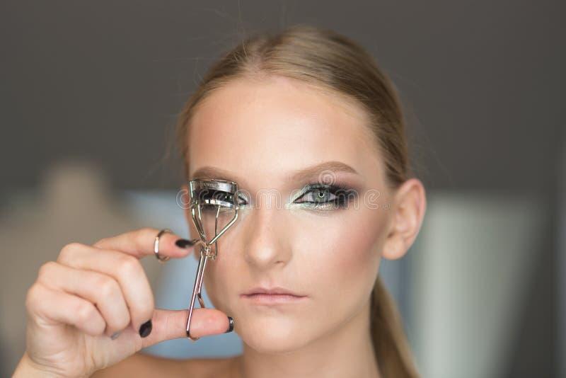 Bigud? de la pesta?a del uso de la mujer para el maquillaje del ojo El rizo de la mujer azota con la herramienta de la belleza, m fotos de archivo libres de regalías