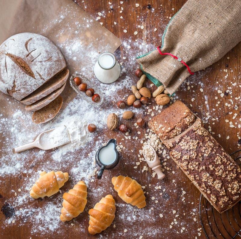 Bij de bakkerij, stilleven met minicroissants, brood, melk, noten en bloem royalty-vrije stock afbeelding